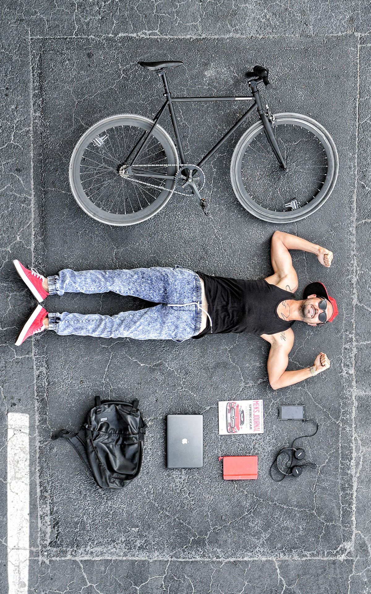 Man and Bike Lie on Concrete